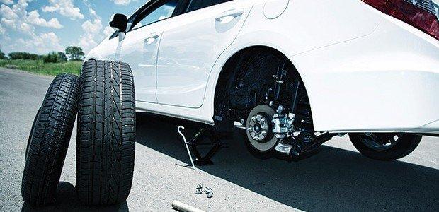 Foto de um carro sem um dos pneus traseiros e um pneu próximo a ele. Imagem para ilustrar a abertura do texto sobre estepe temporário