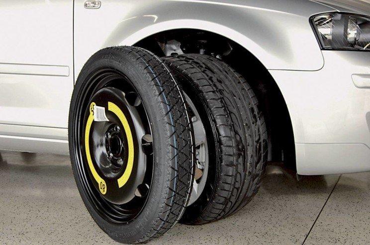 Foto mostra a parte traseira de um carro com dois pneus ao seu lado. Imagem para ilustrar o texto sobre estepe temporário