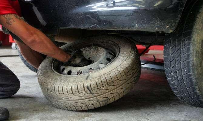 Foto que mostra um homem realizando a troca de pneu em um carro. Imagem para ilustrar o texto sobre estepe temporário