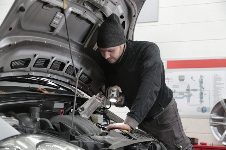 A foto mostrar um homem mexendo na bateria de um carro. A imagem ilustra o texto sobre validade da gasolina