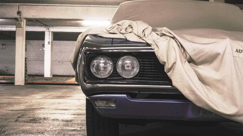 A foto mostra um carro antigo em uma garagem, com um pano em cima dele mostrando apenas aum pedaço da parte da frente. A imagem ilustra o texto sobre validade da gasolina