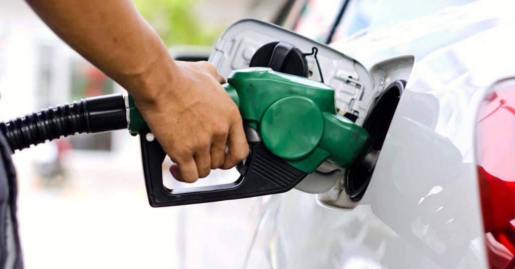 A foto mostrar uma pessoa enchendo um tanque de carro com gasolina. A imagem ilustra o texto sobre dicas para economizar combustível