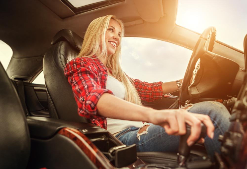 Foto de uma mulher com a mão no câmbio do carro. Imagem para ilustrar o texto sobre câmbio automático