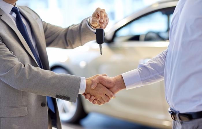 Duas mãos se cumprimentando e um homem entregando a chave do carro. Foto para ilustrar o texto sobre garantia de carro